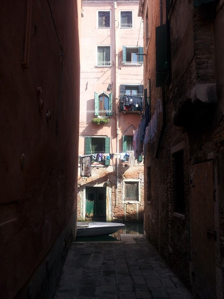 Washing hangs above a canal in Venice Italy